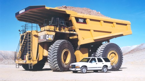 Caterpillar 797 parked next to a regular SUV for size reference.
